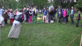 play : BIRZAI, LITHUANIA - JUNE 23, 2014: active children play sack race in city park with big people audience on June 23, 2014 in Birzai, Lithuania. Full HD 1080p.