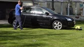 trabalho : VILNIUS,LITHUANIA - APRIL 26, 2014: Worker man wash Ford Focus car automobile with strong water jet on garden lawn in summer on April 26, 2014 in Vilnius, Lithuania. Vídeos