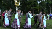 expression : BIRZAI, LITHUANIA - JUNE 23, 2014: young people pairs in national clothes bring burning torch and candles on June 23, 2014 in Birzai, Lithuania. Feast of St John. Shot on Canon XA25. Tripod. Stock Footage