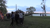 heat : BIRZAI, LITHUANIA - JUNE 23, 2014: turn view of lake and crowd people around big log stacked campfire on field on June 23, 2014 in Birzai, Lithuania. Canon XA25. Tripod.