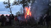 relax : BIRZAI, LITHUANIA - JUNE 23, 2014: People warm surround big fireplace and celebrate national John day on June 23, 2014 in Birzai, Lithuania. Zoom out shot on Canon XA25. Full HD 1080p. Tripod. Stock Footage