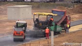 steamroller : VILNIUS, LITHUANIA - NOVEMBER 17, 2014: Truck, asphalt spread and roller machines on November 17, 2014 in Vilnius, Lithuania. Road paver workers with special equipment. Static shot on Canon XA25.