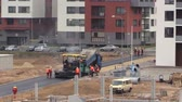 steamroller : VILNIUS, LITHUANIA - NOVEMBER 17, 2014: Asphalt spreader and roller machines on November 17, 2014 in Vilnius, Lithuania. Road pavers workers with special equipment. Zoom out shot on Canon XA25. Stock Footage