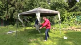 moskitiera : People fix garden tent bower long metal legs. Protection from sun rain and mosquitos insect in nature. Full HD 1080p. Progressive scan 25fps. Tripod.