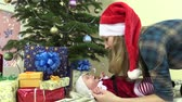 box : Playful mother with Santa hat play with infant daughter baby in christmas festive dress. Fir tree with presents. Sliding forward shot. Full HD 1080p. Dolly camera movement.