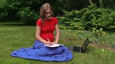 working parents : Beautiful pregnant woman look at laptop computer and write in notebook on green garden grass. Right side sliding shot on Canon XA25. Full HD 1080p. Progressive scan 25fps. Dolly camera movement. Stock Footage