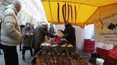 yıllık : VILNIUS LITHUANIA  MARCH 06 2015: Vendor fisher sell smoked fish for customers people in outdoor tent stall at yearly annual festival fair on March 06 2015 in Vilnius Lithuania. 4K UHD Stok Video