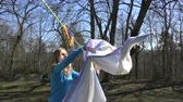 forest : Blond girl woman hang laundry on clothesline strings on background of forest and blue sky. 4K UHD video clip. Stock Footage