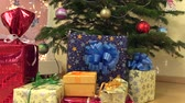 pack : Colorful gift present boxes with ribbons under decorated christmas fir tree with balls toys and white light blinking garland. Sliding forward shot. Full HD 1080p. Dolly camera movement. Stock Footage