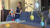мама : Blond mother have fun with newborn baby daughter in orange body cloth on blue sofa. Woman give infant child toy. Easter decorations on table. Focus change shot. 4K UHD video clip. Стоковые видеозаписи