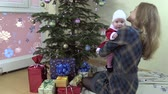 мама : Cheerful mother with lovely baby girl on her hands have fun near fir tree. Infant with Christmas clothes. Static shot. Full HD 1080p. Progressive scan 25fps. Tripod. Стоковые видеозаписи