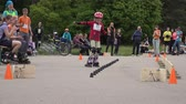 emberek : VILNIUS, LITHUANIA - MAY 23:  zoom out of small girl ride slowly with roller skate around cone on May 23, 2015 in Vilnius, Lithuania. 4K UHD video clip. Roller-skaters amateur race.
