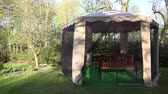 moskitiera : Garden gazebo arbor bower protective net from insect move in wind in spring time. Wooden tables and benches inside. Static shot. 4K UHD video clip. Wideo