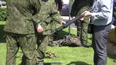 nato : SIRVINTOS, LITHUANIA - JUNE 29: Man hold real machine gun weapon and discuss with professional soldiers on June 29, 2015 in Sirvintos, Lithuania. Demonstration army show. Tilt up shot. 4K
