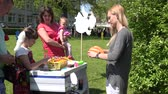 color : SIRVINTOS, LITHUANIA - MAY 29: balloon seller woman make animal shaped balloon for girl in park on May 29, 2015 in Sirvintos, Lithuania. 4K UHD video clip.