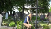 pedra tumular : young sad lonely woman sit near metallic cross in cemetery. 4K UHD video clip.