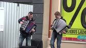 accordionist : VILNIUS, LITHUANIA - MAY 16: two young happy student musician perform with accordion on street on May 16, 2015 in Vilnius, Lithuania. 4K UHD video clip. Annual music street day on May. Stock Footage