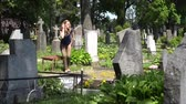 shrink : Young girl visit fellow lover man grave in cemetery. Woman sit on bench near tomb in graveyard. Static shot. 4K