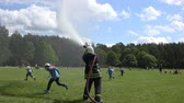 mangueira : VILNIUS, LITHUANIA - MAY 31,2015: Firefighter with hose spray water under cheerful children on May 31, 2015 in Vilnius, Lithuania. National children day. Static shot. 4K