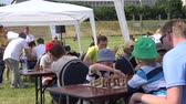 chess board : VILNIUS, LITHUANIA - JUNE 07, 2015: Children with parents play chess in free outdoor tournament on June 07, 2015 in Vilnius, Lithuania. Intelligent game. Static shot. 4K