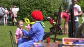peruca : SIRVINTOS, LITHUANIA - MAY 29, 2015:  clown paint with colors on little girl face in green park on May 29, 2015 in Sirvintos, Lithuania. 4K UHD video clip. Fun entertainment for children Vídeos