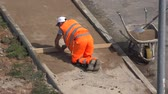 pavimentação : VILNIUS, LITHUANIA - JUNE 02, 2015: construction worker prepares the basis for new footway on June 02, 2015 in Vilnius, Lithuania. 4K UHD video clip. Stock Footage