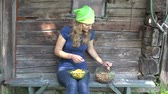 krajina : Beautiful gardener woman with headscarf clean yellow chanterelle mushrooms near rusty wooden house. Static shot. 4K