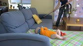 vácuo : mother clean dust from couch with vacuum hoover and little baby daughter play near. 4K UHD