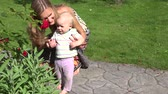 finding : Happy woman with her infant baby walk first steps and expose beauty of rose flower bloom in garden. Woman share knowledge with interested infant child finding new discoveries. Static closeup shot. 4K