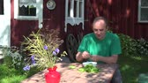 krajina : young happy man hulled green peas pod and eat peas. Old home and flower background in summertime. 4K UHD video clip.