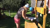 drench : Poor country girl wash baby clothes in bowl in village house yard. Static shot. 4K