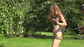 tubos : young smiled man watering woman in swimsuit with water hose in green park. Leisure and summer spree in nature. 4K UHD video clip.
