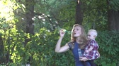 bubble : Nanny woman blow soap bubbles and baby girl look at them in beautiful sunset light in park. Static shot.
