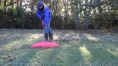 otthonos : man with rake tool raking leaves outside on cold fall day in yard. Static shot.