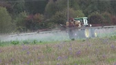 pulverização : PANEVEZYS, LITHUANIA - OCTOBER 03, 2015: agricultural machine spray stubble field near autumn forest trees on October 03, 2015 in Panevezys, Lithuania. Static shot. 4K Vídeos