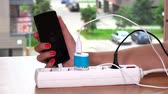 energized : woman hand plug charger cable in extension socket and hold charging phone
