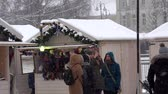 ter : VILNIUS, LITHUANIA - NOVEMBER 30, 2016: Young woman take selfy near holiday fair kiosk in christmas town. Blizzard snow falling in winter season. 4K