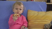 big apple : Attractive young girl taking bite from big red apple at home. Stock Footage