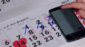 planejador : Female hand compare smart phone android calendar with paper calendar Vídeos