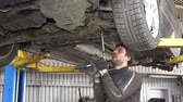 levantado : Male auto mechanic with spanner working under car in garage