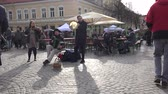 accordionist : VILNIUS, LITHUANIA - MARCH 04, 2017: Musicians play with accordion drum and violin in street event. Handheld steadicam flycam movement shot. 4K UHD Stock Footage