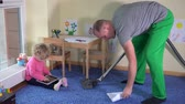 working parents : Man hoover child room and little girl play with tablet computer sitting on floor Stock Footage