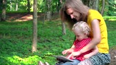 Babysitter woman with cute baby girl using tablet computer in park Wideo