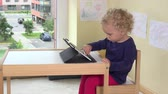Happy blond girl touching tablet computer screen with finger