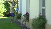 man watering flower in pot hanging on wall house at summer. 4K