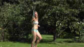 Playful sexy woman spraying herself with water on hot summer day holding hose above. 4K