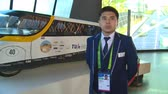 handheld : ASTANA, KAZAKHSTAN - July 8, 2017: male guide showing automobile car prototype powered solar sun cell energy in Expo 2017 exhibition. Handheld shot. Stock Footage