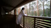 roupão de banho : young girl goes to the balcony in white Bathrobe