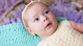 постельные принадлежности : little baby girl lying on a bed cradle with purple and turquoise fur knitted cape