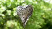 windy : iron heart hanging on a chain on a background of green trees Stock Footage